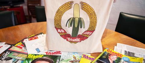 Eine Jubiläums-Stofftasche und einige Ausgaben des Satiremagazins Titanic liegen auf dem Konferenztisch in den Redaktionsräumen.
