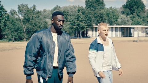 Foto aus dem Film: Zwei junge Männer laufen über einen Platz.