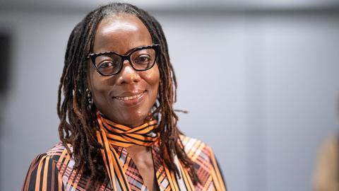 Eine Frau mit dunklen Dreadlocks und Brille steht vor einem grauen Hintergrund und lächelt in die Kamera.