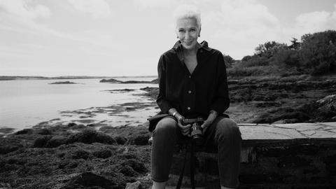 Das Schwarz-weiß-Bild zeigt eine Frau mit kurzen hellen Haaren, die auf einer Mauer sitzt. Sie hält eine Kamera. Im Hintergrund ist das Meer zu sehen.