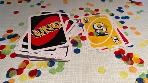 Uno Karten liegen auf einem Tisch, buntes Konfetti drumherum