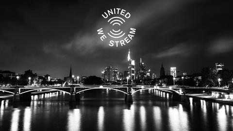 """Skyline von Frankfurt vom Main aus fotografiert - im Himmel schwebt das Logo von """"United We Stream"""""""