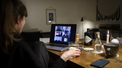 Eine Frau sitzt während der Corona-Pandemie an einem Tisch in ihrer Wohnung vor einem Laptop, während sie mit weiteren fünf Personen an einer Videokonferenz mit der Videokonferenzanwendung «Zoom» teilnimmt.