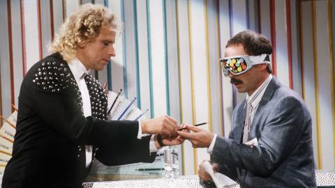 """Noch ist Moderator Thomas Gottschalk (l) völlig ahnungslos: Behutsam reicht er bei """"Wetten dass"""" am 3.8.1988 seinem Wettkandidaten Bernd Fritz einen Buntstift"""