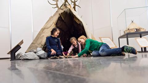 """Blick in die Ausstellung """"Eiszeit-Safari"""" - Kinder sitzen in einem Zelt"""