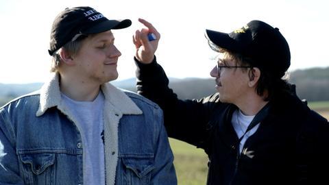 Zwei junge Männer mit Basecaps albern herum