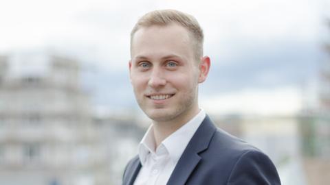 Ein junger Mann mit blonden Haaren lächelt in die Kamera. Er trägt einen Anzug.