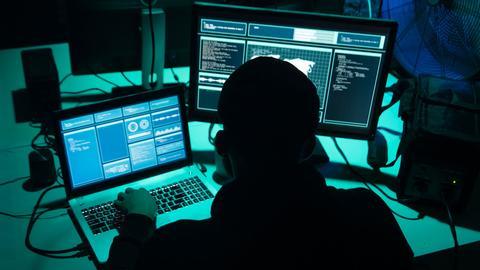 eine Person sitzt vor zwei Computer-Bildschirmen im Dunkeln