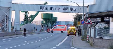 """EIn Blick in die Straße und das Werk in den Morgenstunden. Auf einer Brücke steht """"Durst Malz-Union Malz""""."""
