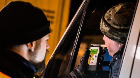 Ein Polizist führt eine Alkoholkontrolle durch