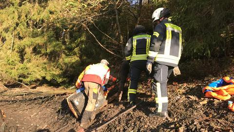 Einsatzkräfte bergen den Tresor aus dem Schlamm.