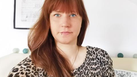Isabell Stark, eine junge Frau mit langen roten Haaren schaut ernst in die Kamera.