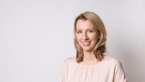 Eine junge Frau mit dunkelblonden Haaren und weißem Oberteil lächelt in die Kamera.