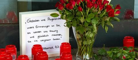 Das Foto zeigt Kerzen, Blumen und Trauerworte vor der Tür.