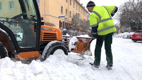 Ein Mann befreit ein Räumfahrzeug vom Schnee