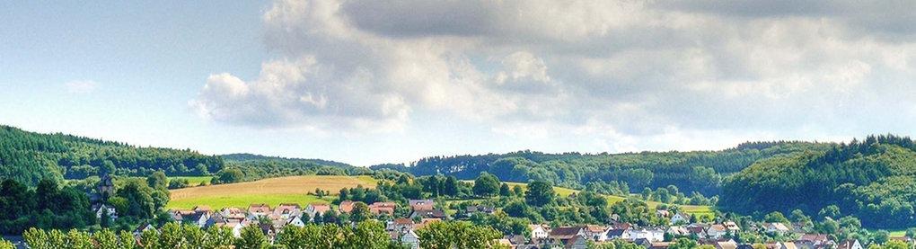 Ein Blick aus der Ferne auf die Gemeinde Lahntal, umgeben von malerischer Landschaft.