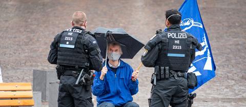 Ein Friedensaktivist wird am Frankfurter Römer von zwei Polizisten angesprochen