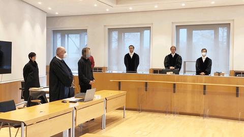 Foto des Gerichtssaals -  mit der angeklagten Person, Anwälten und Richter, alle stehend.