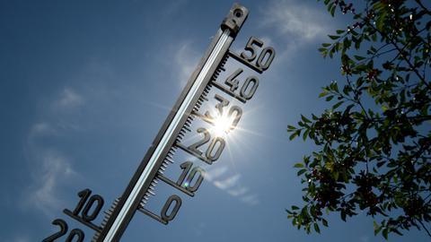 Vor einem strahlend blauen Himmel mit gleißendem Sonnenlicht ist ein Thermometer zu sehen.