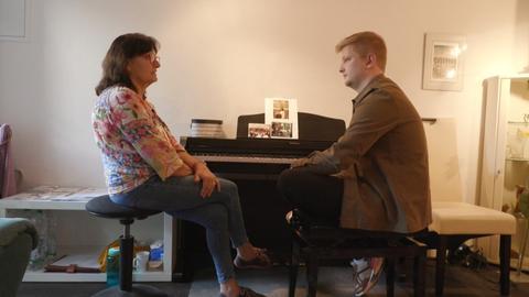 hr-Reporter Simon Rustler sitzt mit Heide an ihrem Klavier - früher war sie seine Klavierlehrerin, heute stellt sie als Jenseitsmedium Kontakt zu Toten her, behauptet sie