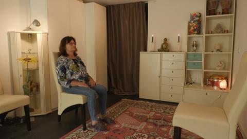Heide sitzt auf einem Stuhl in ihrem Studio und hat die Augen zu - so, behauptet sie, sieht es aus, wenn sie sich mit der geistigen Welt verbindet