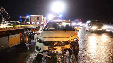 Ein Auto mit beschädigter Front steht im Dunkeln auf einer Autobahn.