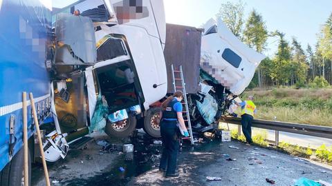 """Das Foto zeigt die Unfallstelle, die von einer Polizistin und einem Polizisten begutachtet wird. Zwei """"Köpfe"""" der LKWs liegen nebeneinander umgekippt auf der Straße."""