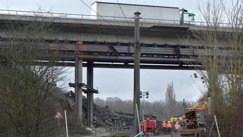 Mitarbeiter einer Baufirma stehen unter der gesperrten A44-Brücke.