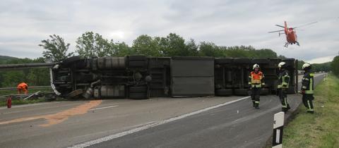 Der umgestürzte Lastwagen an der Unfallstelle, der alle Fahrspuren blockiert.