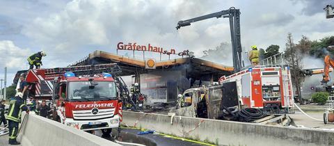 Feuerwehrmänner und -frauen, Feuerwehrautos, ein Lösch-Kran umrahmen die abgebrandte und in Schutt liegende Raststätte Gräfenhausen Ost.
