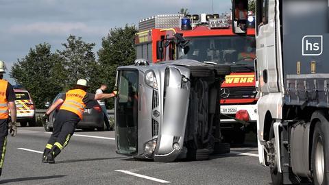 Ein Auto, das auf der A5 vom schleudernden Anhänger eines Kleinlasters erfasst wurde, liegt auf die Seite gekippt auf der Autobahn