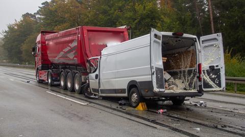 Ein weißer Kleintransporter, der gegen das Heck eines vor ihm fahrenden roten Muldenkippers gekracht ist.