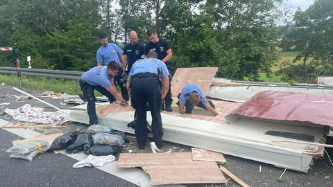 Polizisten wühlen in den Trümmern eines verunfallten Wohnmobils auf der Suche nach Drogen