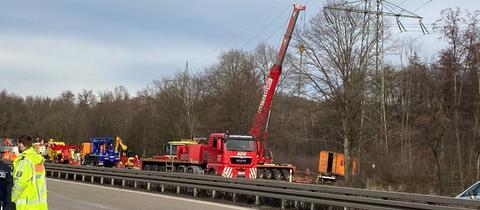 Ein Kran hilft bei der Bergung des verunglückten Lkw, der einen Strommasten neben der A661 bei Offenbach gerammt hat