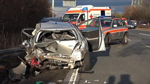 Das Wrack eines der beteiligten Fahrzeuge, Rettungskräfte