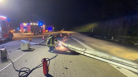 Ein Feuerwehrmann zersägt auf der A7 die herausgerissene Leitplanke.
