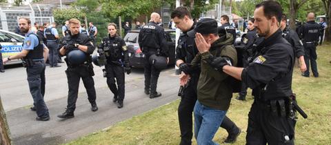 Polizeibeamte führen vor dem Abschiebegefängnis einen jungen Mann ab.