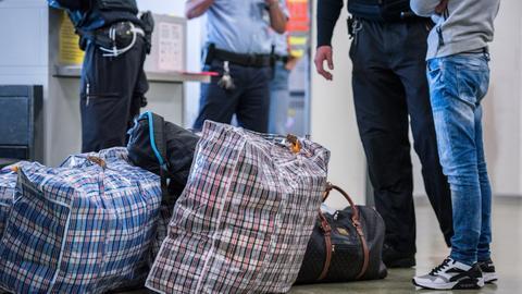 Ein Mann steht vor seiner Abschiebung mit Gepäck am Flughafen. (Symbolbild)