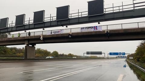 Polizisten und Aktivisten mit Transparenten auf A5-Brücke.