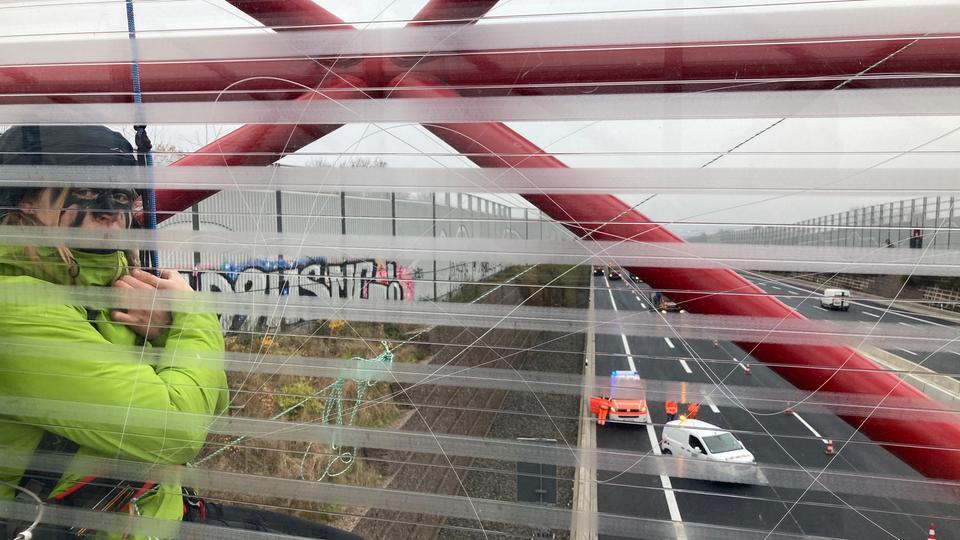 Eine Aktivistin hängt an einem Seil an einer Brücke an der A7 bei Kassel.