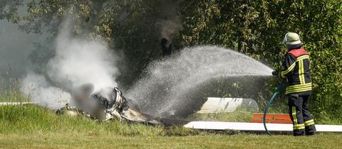 Foto des abgestürzten Segelflugzeuges in Fulda. Ein Feuerwehrmann löscht.