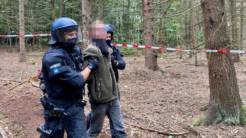 Die Polizei führt einen Aktivisten im Herrenwald ab.