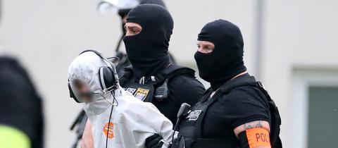 Ali B. wird von Beamten einer Spezialeinheit zu einem Polizeihubschrauber gebracht.