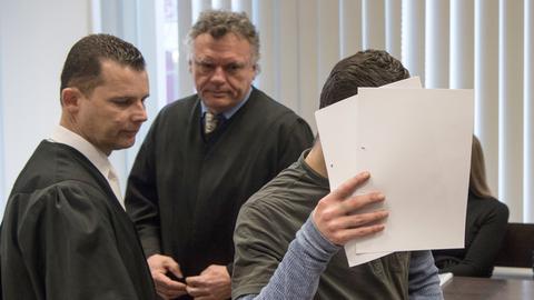 Ali B. verdeckt mit Zetteln sein Gesicht, neben ihm seine Anwälte