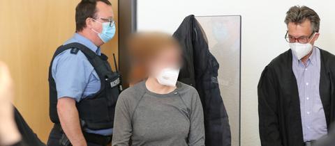Die Angeklagte steht in einem Gerichtssaal neben ihrem Verteidiger Tronje Döhmer (r).
