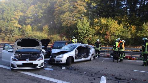 Einsatzkräfte stehen um die beschädigten Autos herum.