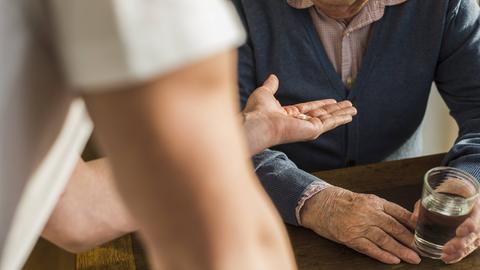 Altenpfleger gibt einem Mann Medizin