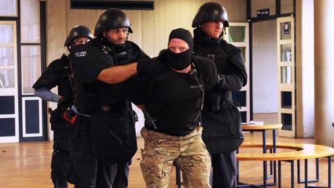 Polizisten führen bei Übung einen der Attentäter ab