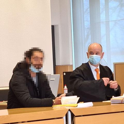 Der Angeklagte und sein Anwalt daneben sitzen im Fuldaer Landgericht an einem Tisch. Daneben ist ein Polizeibeamter von hinten zu sehen.