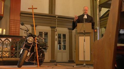 Pfarrer mit Motorrad in Kirche